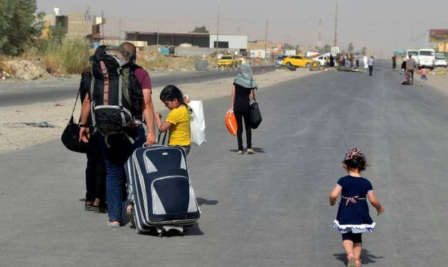 In this Sunday, June 29, 2014 photo, an Iraqi family leave their hometown Mosul, walking towards Irbil, on the outskirts of the northern city of Mosul, Iraq. The al-Qaida breakaway group that has seized much of Syria and Iraq has formally declared the establishment of a new Islamic state, demanding allegiance from Muslims worldwide in a move that could further strain relations with other militant groups. (AP Photo)