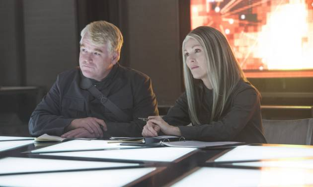 "This photo released by Lionsgate shows, Philip Seymour Hoffman, left, as Plutarch Heavensbee and Julianne Moore as President Coin in a scene from the film, ""The Hunger Games: Mockingjay - Part 1."" The movie releases on Nov. 21, 2014. (AP Photo/Lionsgate, Murray Close)"