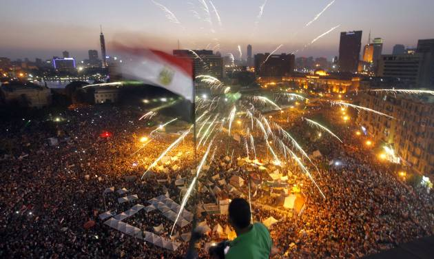 An Egyptian protester waves a national flag as Egyptians gather in Tahrir Square during a demonstration against President Mohammed Morsi in Cairo, Sunday, June 30, 2013. Hundreds of thousands of opponents of Egypt's Islamist president poured out onto the streets in Cairo and across much of the nation Sunday, launching an all-out push to force Mohammed Morsi from office on the one-year anniversary of his inauguration. Fears of violence were high, with Morsi's Islamist supporters vowing to defend him. (AP Photo/Amr Nabil)
