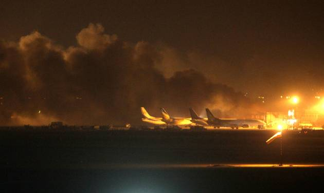 Fire illuminates the sky above the Jinnah International Airport in Karachi where security forces are fighting with attackers Sunday night, June 8, 2014, in Pakistan. Gunmen disguised as police guards attacked a terminal with machine guns and a rocket launcher during a five-hour siege that killed a number of people as explosions echoed into the night, while security forces retaliated and killed all the attackers, officials said Monday. (AP Photo/Fareed Khan)