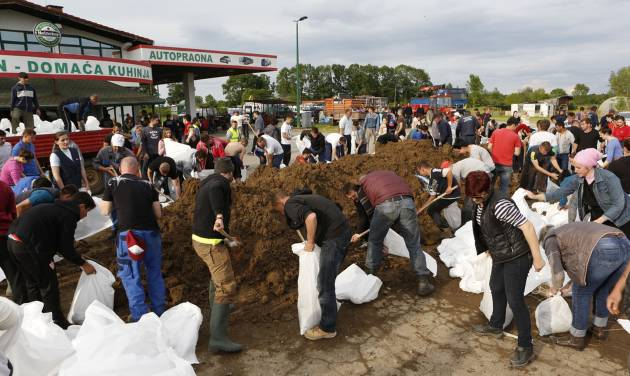 Bosnian people prepare sandbags to protect the city from flooding near Orasje 200 kms north of Sarajevo, on Sunday May 18, 2014. Packed into buses, boats and helicopters, carrying nothing but a handful of belongings, tens of thousands fled their homes in Bosnia and Serbia, seeking to escape the worst flooding in a century. (AP Photo/Amel Emric)