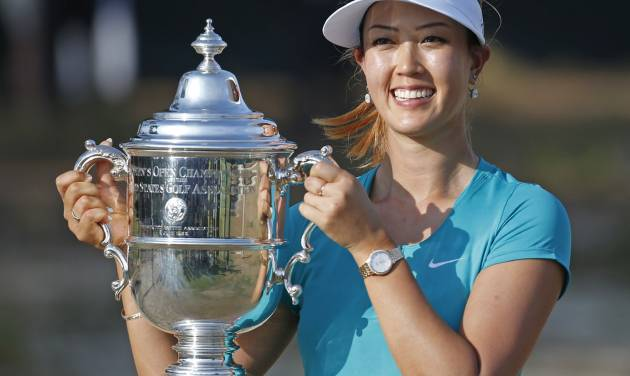 FILE - In this June 22, 2014 file photo, Michelle Wie poses with the trophy after winning the U.S. Women's Open golf tournament in Pinehurst, N.C. The 24-year-old from Hawaii is ready to put her first major championship behind her. Wie is among the favorites when the Ricoh Women's British Open gets underway Thursday, July 10, 2014, at Royal Birkdale.  (AP Photo/John Bazemore, File)