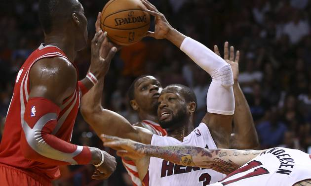 Houston Rockets' Dwight Howard (left) and Terrenc Jones (6) force Miami Heat's Dwyane Wade (3) to pass the ball during the first half of an NBA  basketball game in Miami, Sunday, March 16, 2014. (AP Photo/J Pat Carter)