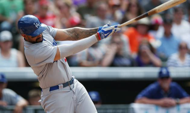 Los Angeles Dodgers' Matt Kemp follows through with his swing after connecting for an RBI-single against the Colorado Rockies in the fifth inning of a baseball game in Denver on Sunday, July 6, 2014. (AP Photo/David Zalubowski)