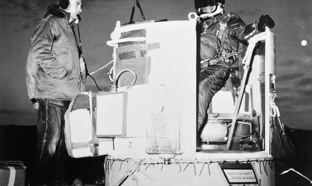FILE - In this Nov. 16, 1959, file photo, provided by the U.S. Air Force, Capt. Joseph Kittinger Jr., aerospace laboratory test director, sits in the open balloon gondola after his first parachute test jump for Project Excelsior at Holloman Air Force Base in Alamogordo, N.M. The gondola carried him at an altitude of 76,400 feet for his record free fall jump of more than 12 miles. At left is David Willard, who designed and developed special equipment for the gondola. On Tuesday, Oct. 9, 2012, if winds allow, in the desert surrounding Roswell, N.M., pilot Felix Baumgartner will attempt to break Kittinger's world record for the highest and fastest free fall. (AP Photo/U.S. Air Force, File)