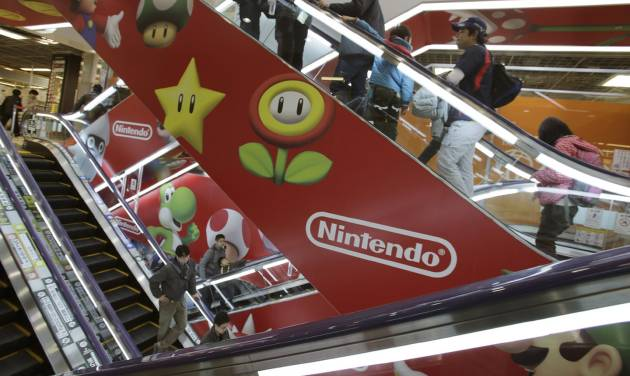FILE - In this Dec. 15, 2013 file photo, shoppers take escalators painted with the logos of Nintendo and Super Mario characters at an electronics store in Tokyo. Nintendo Co. sank to a worse-than-expected loss for the fiscal first quarter on lagging Wii U and 3DS video-game machine sales. But the Japanese company behind Super Mario and Pokemon games stuck to its annual forecasts Wednesday, July 30, 2014 for a 20 billion yen ($196 million) profit on 590 billion yen ($5.8 billion) sales. (AP Photo/Shizuo Kambayashi, File)