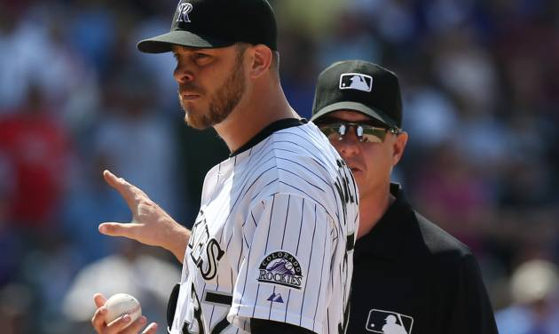 After being ejected from the game for hitting Atlanta Braves' Evan Gattis with a pitch, Colorado Rockies relief pitcher Nick Masset, front, hands the ball to third base umpire Paul Emmel in the ninth inning of the Rockies' 10-3 victory in a baseball game in Denver on Thursday, June 12, 2014. (AP Photo/David Zalubowski)