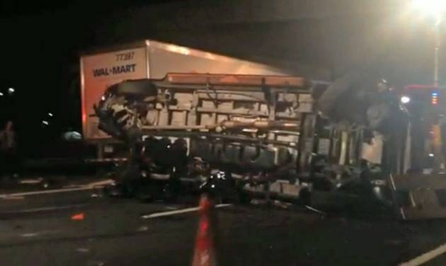 In this image from video the limousine bus carrying Tracy Morgan and six other people lies on it's side early Saturday morning, June 7, 2014, on the New Jersey Turnpike. A New Jersey highway crash that severely injured Tracy Morgan and killed another comedian is drawing attention to the dangers of tired truckers just as the industry and its allies in Congress are poised to roll back safety rules on drivers' work schedules.  (AP Photo/Will Vaultz Photography)