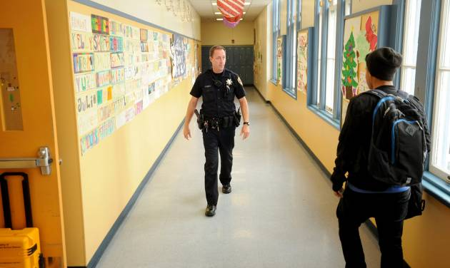 FILE - In this Dec. 17, 2012 photo, Officer Rick Moore of the Oakland school district police patrols Oakland Technical High School in Oakland, Calif. The National Rifle Association on Friday, Dec. 21 2012 called for the placement of an armed police officer in every school, but parents and educators questioned how safe such a move would keep kids, whether it would be economically feasible and how it would alter student life. Their reactions ranged from supportive to disgusted. (AP Photo/Noah Berger, File)