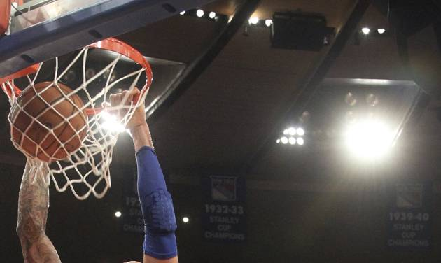 New York Knicks' Tyson Chandler, left, dunks the ball as Orlando Magic's Nikola Vucevic watches during the first half of an NBA basketball game Wednesday, Jan. 30, 2013, at Madison Square Garden in New York.  (AP Photo/Mary Altaffer)