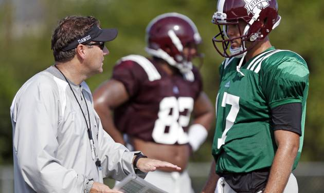 Mississippi State quarterback Tyler Russell, right, confers with football coach Dan Mullen during an NCAA college football practice in Starkville, Miss., Saturday, Aug. 10, 2013. High humidity mixed with high temperatures have marked most of the football training camps this summer. (AP Photo/Rogelio V. Solis)  ORG XMIT: MSRS102