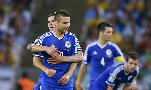 Bosnia's Vedad Ibisevic, front left, is congratulated by a teammate after scoring his side's first goal during the group F World Cup soccer match between Argentina and Bosnia at the Maracana Stadium in Rio de Janeiro, Brazil, Sunday, June 15, 2014.  (AP Photo/Kirsty Wigglesworth)