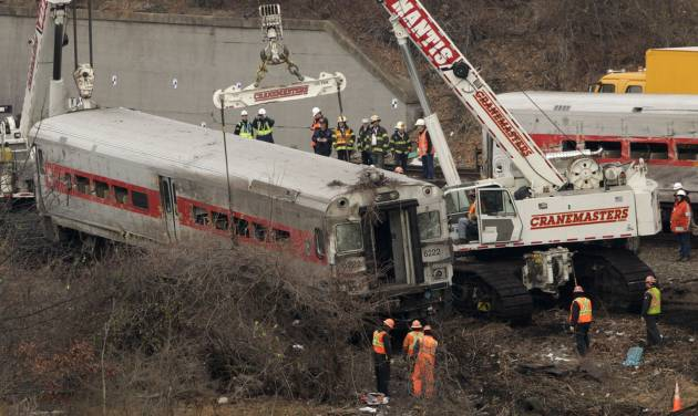 "Cranes salvage the last car from from a train derailment in the Bronx section of New York, Monday, Dec. 2, 2013.  Federal authorities began righting the cars Monday morning as they started an exhaustive investigation into what caused a Metro-North commuter train rounding a riverside curve to derail, killing four people and injuring more than 60 others. A second ""event recorder"" retrieved from the train may provide information on the speed of the train, how the brakes were applied, and the throttle setting, a member of the National Transportation Safety Board said Monday.   (AP Photo/Mark Lennihan)"