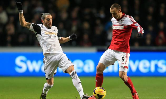 Fulham's Dimitar Berbatov, right, and Swansea City's Chico battle for the ball during their English Premier League soccer match at the Liberty Stadium, Swansea, Wales, Tuesday, Jan. 28, 2014. (AP Photo/Nick Potts, PA Wire)   UNITED KINGDOM OUT  -  NO SALES  -  NO ARCHIVES