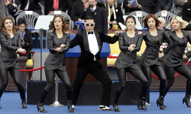 """FILE - In this Monday, Feb. 25, 2013 file photo, South Korean rapper PSY, third left, performs with dancers before the inauguration ceremony of President Park Geun-hye at the National Assembly in Seoul, South Korea. South Korean rapper PSY is unveiling his much-awaited follow-up to """"Gangnam Style"""" next month and celebrating it with a huge concert in Seoul. PSY made the announcement Friday, March 8, on YouTube where his Gangnam Style music video has a record 1.39 billion views. PSY says he will release the new single and hold the concert at a soccer stadium both on April 13. (AP Photo/Lee Jin-man, File)"""