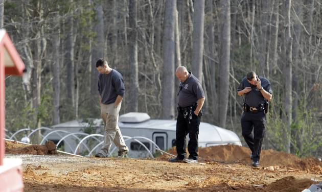 A man, left, walks with investigators Monday, April 8, 2013, around the scene of a collapsed construction site where two children died when the dirt walls collapsed Sunday on Cedarbrook Court in Stanley, N.C. (AP Photo/Bob Leverone)