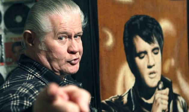 """FILE - In this Dec. 9, 2009 file photo, Paul MacLeod stands before a poster of Elvis Presley in the antebellum home and a private Elvis Presley museum he calls """"Graceland Too,"""" in Holly Springs, Miss. MacLeod, a lifetime Elvis fanatic, was found dead on the porch of his home early Thursday, July 17, 2014, two days after authorities say he shot and killed a man who forced his way into the attraction. (AP Photo/Rogelio V. Solis, File)"""