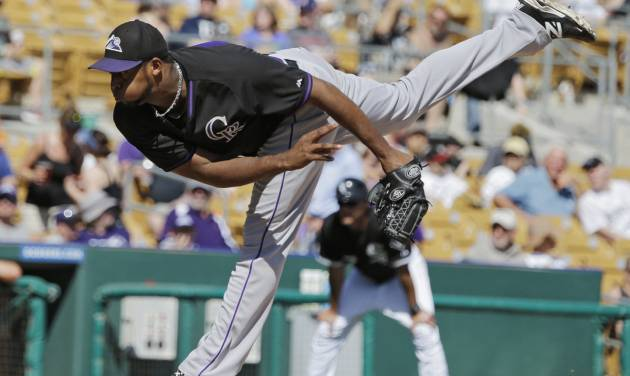 Colorado Rockies starting pitcher Juan Nicasio follows through on a pitch against the Chicago White Sox in the fifth inning of a spring exhibition baseball game Tuesday, March 25, 2014, in Glendale, Ariz. (AP Photo/Mark Duncan)