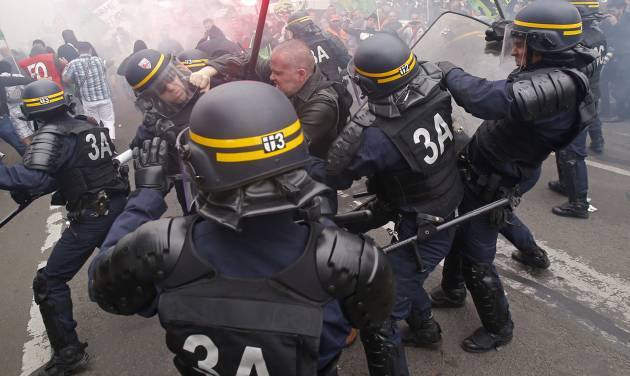 French riot police clash with a striking train workers, during a protest over a bill to reform the state-run railway system in Paris, Tuesday, June 17, 2014. A weeklong strike by rail workers has caused one of the worst disruptions to the country's rail network in years and is heating up as the reform bill goes to the lower house of Parliament for debate Tuesday. (AP Photo/Michel Euler)