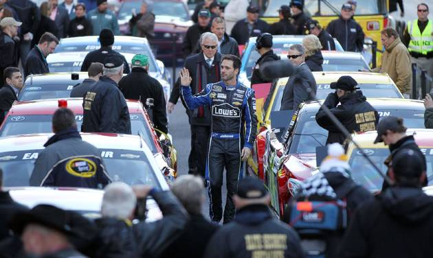 Jimmie Johnson waves to the crowd as he is introduced before leading a victory lap on the Las Vegas Strip during NASCAR Champions Week on Thursday, Dec. 5, 2013, in Las Vegas. (AP Photo/Isaac Brekken)
