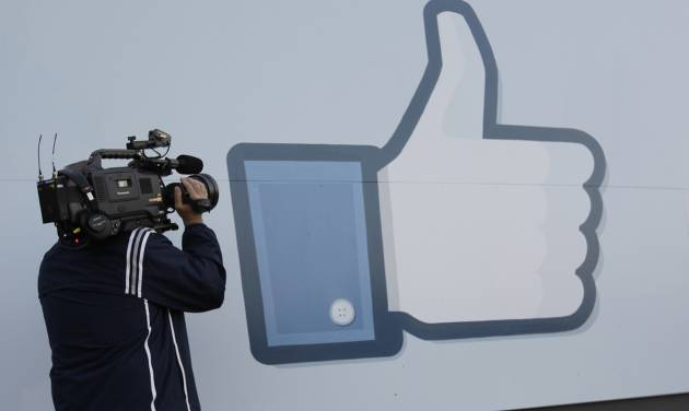 A television photographer shoots the Like sign outside of Facebook headquarters in Menlo Park, Calif., Friday, May 18, 2012. Facebook CEO Mark Zuckerberg symbolically opened trading on the Nasdaq stock market inside Facebook headquarters in Menlo Park. Facebook stock is starting trading today, available to the general public for the first time. The social networking site, which was started in a college dorm room eight years ago, would be valued at more than $100 billion according to the price set for shares ahead of today's trading. (AP Photo/Paul Sakuma)