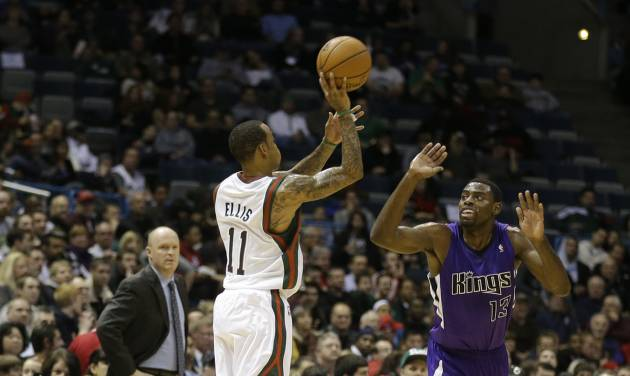 Milwaukee Bucks' Monta Ellis (11) hits a half-court shot at the end of the first quarter as Sacramento Kings' Tyreke Evans(13) defends during a NBA basketball game on Wednesday, Dec. 12, 2012, in Milwaukee. Bucks head coach Scott Skiles, left, watches the play. (AP Photo/Jeffrey Phelps)