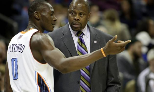 Charlotte Bobcats center Bismack Biyombo, left, talks with head coach Patrick Ewing in the first half of an NBA basketball game against the New York Knicks in Charlotte, N.C., Friday, Nov. 8, 2013. Ewing coached the team instead of Steve Clifford who was hospitalized. New York won 101-91. (AP Photo/Nell Redmond)