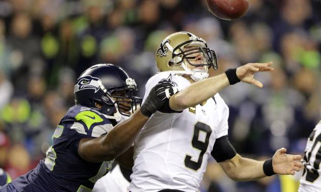 FILE - In this Dec. 2, 2013, file photo, Seattle Seahawks defensive end Cliff Avril hits the arm of New Orleans Saints quarterback Drew Brees causing a fumble that was returned for a touchdown by Seahawks defensive end Michael Bennett in the first half of an NFL football game in Seattle. The Seahawks finished the regular season as the best pass defense in the NFL with three All-Pro selections in the secondary. Their best performance came when they suffocated New Orleans in Week 13. Now comes the challenge of duplicating that in Saturday's NFC divisional playoff game against the Saints. (AP Photo/Scott Eklund, File)