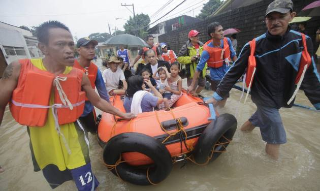 Residents are evacuated by rescuers in Marikina, east of Manila, Philippines, Tuesday Aug. 7, 2012. Relentless rains submerged half of the sprawling Philippine capital, triggered a landslide that killed eight people and sent emergency crews scrambling Tuesday to rescue and evacuate tens of thousands of residents. (AP Photo/John Javellana)
