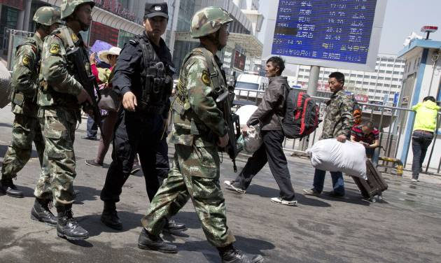"Heavily armed Chinese paramilitary policemen march past the site of the Wednesday's explosion outside the Urumqi South Railway Station in Urumqi in northwest China's Xinjiang Uygur Autonomous Region Thursday, May 1, 2014. Chinese President Xi Jinping has demanded 'decisive actions"" against terrorism following the attack at the railway station in the far west minority region of Xinjiang that left three people dead and 79 injured. (AP Photo/Ng Han Guan)"
