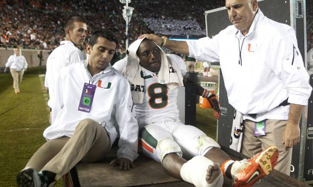 Miami running back Duke Johnson is consoled as he is taken off the field after injuring his foot during the third quarter of an NCAA college football game against Florida State on Saturday, Nov. 2, 2013, in Tallahassee, Fla. (AP Photo/Phil Sears)