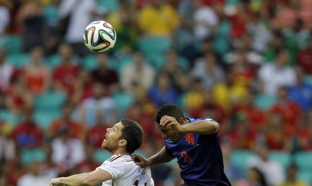 Spain's Xavi goes up for the ball against Netherlands' Terence Kongolo during the first half of the group B World Cup soccer match between Spain and the Netherlands at the Arena Ponte Nova in Salvador, Brazil, Friday, June 13, 2014.  (AP Photo/Natacha Pisarenko)