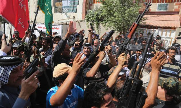 Iraqi Shiite tribal fighters raise their weapons and chant slogans against the al-Qaida inspired Islamic State of Iraq and the Levant (ISIL) in Baghdad's Sadr city, Iraq, Saturday, June 14, 2014. Thousands of Shiites from Baghdad and across southern Iraq answered an urgent call to arms Saturday, joining security forces to fight the Islamic militants who have captured large swaths of territory north of the capital and now imperil a city with a much-revered religious shrine. (AP Photo/Karim Kadim)