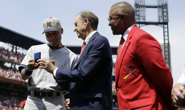 New York Yankees shortstop Derek Jeter, left, is presented with a pair of cufflinks by St. Louis Cardinals Bill DeWitt Jr., center, and former Cardinals Hall of Fame shortstop Ozzie Smith, right, during a ceremony before the start of a baseball game between the Yankees and Cardinals Monday, May 26, 2014, in St. Louis. (AP Photo/Jeff Roberson)