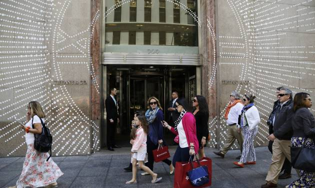 In this Monday, May 19, 2014 photo, shoppers walk by Tiffany & Company's Fifth Avenue store in New York. The upscale jeweler known for its blue boxes reports earnings Wednesday, May 21, 2014. (AP Photo/Mark Lennihan)