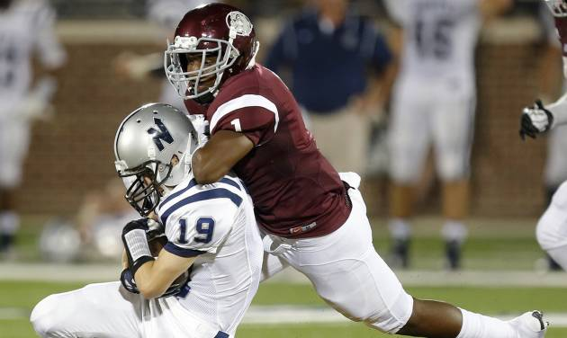Edmond Memorial's Ashton Antwine brings down Edmond North's Carson Taber during their high school football game at Wantland Stadium in Edmond, Friday, September 6, 2013. Photo by Bryan Terry, The Oklahoman