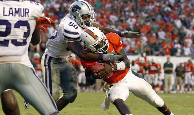Miami quarterback Jacory Harris, right, is stopped at the goal line by Kansas State's Tre Walker in the final minute of an NCAA college football game against Kansas State, Saturday, Sept. 24, 2011, in Miami. Kansas State defeated Miami 28-24. (AP Photo/The Miami Herald, Al Diaz) MAGS OUT ORG XMIT: FLMIH112