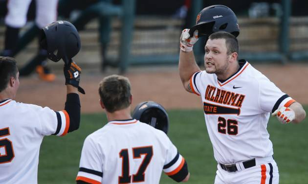 Oklahoma State's Zach Fish (26) reacts with teammates after hitting a grand slam during the bedlam matchup between the University of Oklahoma and Oklahoma State University in the Phillips 66 Big 12 Baseball Championship in Oklahoma City, Okla. on Wednesday, May 21, 2014.   Photo by Chris Landsberger, The Oklahoman