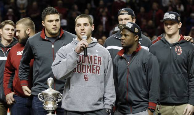 Surrounded by his teammates, OU quarterback Trevor Knight addresses the crowd at halftime of a Sooner basektball game earlier this season.                    Photo by Nate Billings, The Oklahoman