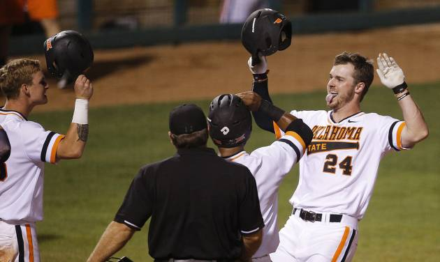 Oklahoma State\'s Conor Costello celebrates as he crosses home plate after hitting a grand slam...