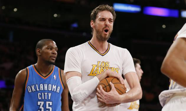 Los Angeles Lakers center Pau Gasol, center, reacts after a foul was called against teammate Ryan Kelley, rear right, as Oklahoma City Thunder small forward Kevin Durant, left, looks on during the first half of an NBA basketball game in Los Angeles, Sunday, March 9, 2014. (AP Photo/Danny Moloshok)