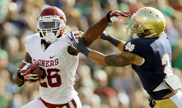 Oklahoma's Damien Williams (26) tries to get past Notre Dame's Bennett Jackson (2) in the first quarter during a college football game between the University of Oklahoma Sooners (OU) and the Notre Dame Fighting Irish at Notre Dame Stadium in South Bend, Ind., Saturday, Sept. 28, 2013. Photo by Nate Billings, The Oklahoman