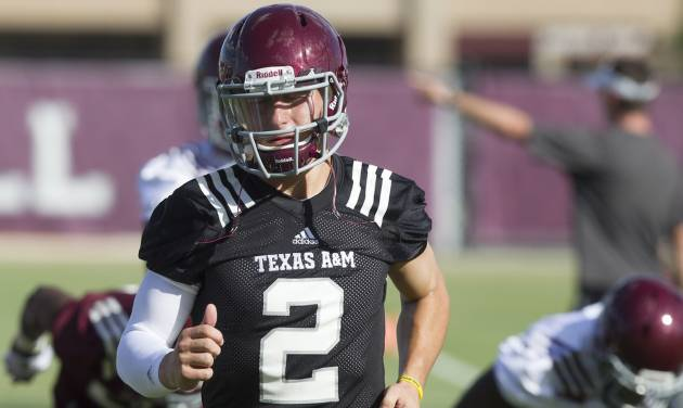 Texas A&M quarterback and Heisman Trophy winner Johnny Manziel warms up during football practice, Monday, Aug. 5, 2013, in College Station, Texas. The NCAA has started an investigation as to whether Manziel received payment for signing hundreds of autographs on photos and sports memorabilia in January. (AP Photo/Patric Schneider)  ORG XMIT: TXPX105