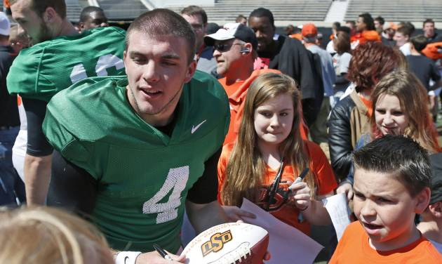 Oklahoma State quarterback J.W. Walsh (4) signs autographs for fans following an Orange Blitz NCAA college spring football practice in Stillwater, Okla., Saturday, April 5, 2014. (AP Photo/Sue Ogrocki)