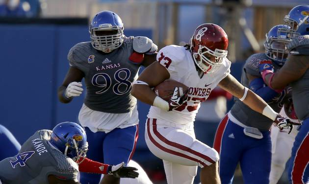 OU's Trey Millard, center, runs past Kansas defenders during a game earlier this season. Millard will miss the remainder of his senior season after suffering a knee injury Saturday against Texas Tech.  Photo by Bryan Terry, The Oklahoman