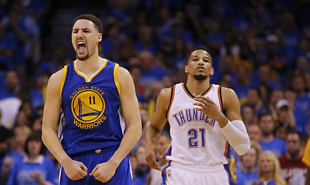 Golden State\'s Klay Thompson (11) reacts in front of Oklahoma City\'s Andre Roberson (21) late in...