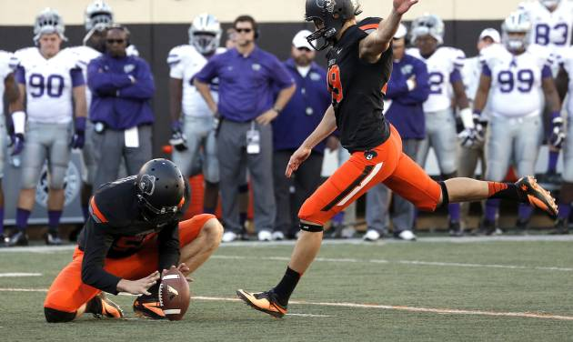 Oklahoma State's Ben Grogan (19) kicks s field goal late in the fourth quarter as Oklahoma State's Michael Reichenstein (59) holds during the second half of a college football game between the Oklahoma State University Cowboys (OSU) and the Kansas State University Wildcats (KSU) at Boone Pickens Stadium in Stillwater, Okla., Saturday, Oct. 5, 2013. OSU won 33-29.Photo by Sarah Phipps, The Oklahoman