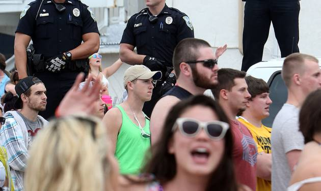 FILE - This March 11, 2014 file photo shows Panama City Beach Police Officers watching over a large crowd of spring breakers during a Luke Bryan concert in Panama City, Fla. (AP Photo/The News Herald/Panama City, Fla., Andrew Wardlow)