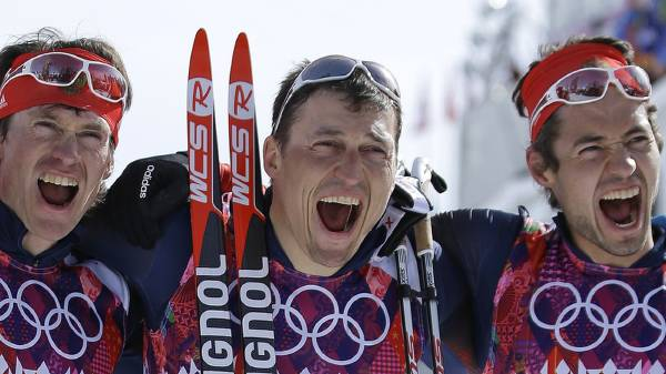 Russia's gold medal winner Alexander Legkov is flanked by Russia's silver medal winner Maxim Vylegzhanin, left, and Russia's bronze medal winner Ilia Chernousov after the men's 50K cross-country race at the 2014 Winter Olympics, Sunday, Feb. 23, 2014, in Krasnaya Polyana, Russia. (AP Photo/Gregorio Borgia)
