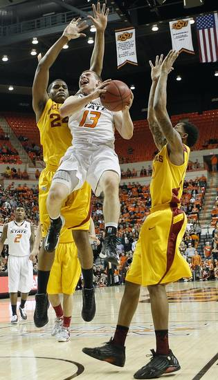 Oklahoma State's Phil Forte (13) drives against Iowa State Cyclones' Percy Gibson (24) and Korie Lucious (13) during the college basketball game between the Oklahoma State University Cowboys (OSU) and the Iowa State University Cyclones (ISU) at Gallagher-Iba Arena on Wednesday, Jan. 30, 2013, in Stillwater, Okla.  Photo by Chris Landsberger, The Oklahoman